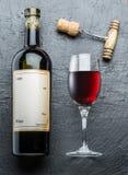 Vinflaskan, vinexponeringsglas och korkskruvet på en grafit stiger ombord royaltyfria bilder