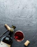 Vinflaskan, vinexponeringsglas och korkskruvet på en grafit stiger ombord arkivfoto