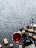 Vinflaskan, vinexponeringsglas och korkskruvet på en grafit stiger ombord arkivbilder