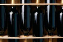 Vinflaskor i träspjällåda på trätabellbakgrund, närbild arkivfoto