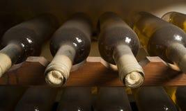 Vinflaskor på hylla Arkivfoton