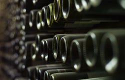 Vinflaskor på väggen av källaren royaltyfria foton