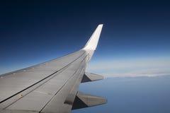 Vinge av en trafikflygplannivå i flykten blå sky arkivbild