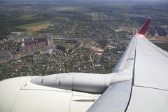 Vinge av flygplanet över staden och husen royaltyfria bilder