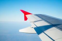 Vingen av ett flygplanflyg ovanf?r morgonen f?rdunklar Flygplanvinge i himlen som ser till och med f?nstret royaltyfri bild