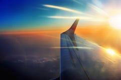 Vingen av flygplanet i soluppgång strålar i flykten Arkivfoton