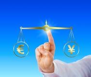 Vinger die de Euro vergelijken bij Pari met Yen Sign Royalty-vrije Stock Afbeeldingen