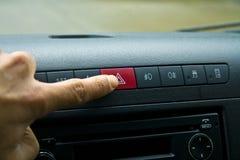 Vinger die het rode lichtknoop van de autonoodsituatie in de auto raken stock afbeelding