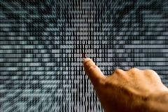 Vinger die op een rood beetje in binaire code richten Stock Afbeelding