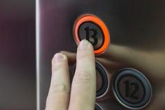 Vinger dringende dertiende verdieping knoop in lift Ongelukkig n stock foto
