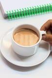Vinger iemand wat betreft kop van koffie, notitieboekje, witte achtergrond stock foto's