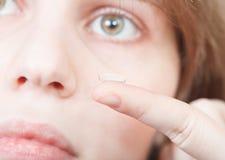 Vinger met correctieve lens en vrouwelijk gezicht stock afbeeldingen