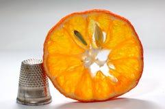 Vingerhoedje en sinaasappel Stock Afbeeldingen