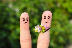 Vingerkunst van paar de man geeft vrouwenbloemen, is zij niet tevreden stock foto
