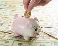 Hand die gouden muntstuk plaatsen in spaarvarken Royalty-vrije Stock Afbeeldingen