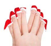 Vingersgezichten in Kerstmanhoeden tegen wit worden geïsoleerd dat Gelukkige vriend Royalty-vrije Stock Foto