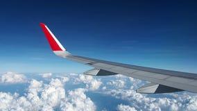 Vingflygplanflyg i himlen Spetsen av vingen är röd Överkanten av nivån är den blåa himlen, och botten är ett vitt moln arkivfilmer