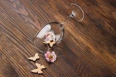 Vinglas med dekorativa blommor och fjärilar Arkivfoto