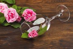Vinglas med dekorativt ljus - rosa rosor Arkivbild