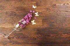 Vinglas med lilor och fjärilar Arkivfoto
