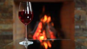 Vinglas med rött vin nära en spis arkivfilmer