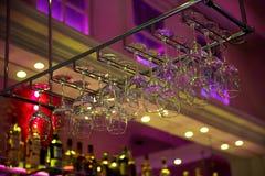 Vinglas och bägare hänger ovanför stångräknaren suddighet bakgrund vektor för musik för bakgrundsfärgman royaltyfri fotografi