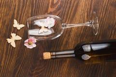 Vinglas och flaska med dekorativa blommor och fjärilar Arkivfoto