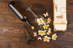 Vinglas och flaska med dekorativa blommor och fjärilar Royaltyfri Bild