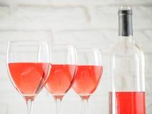 Vinglas tre med rosa vin och flaskan på vit bakgrund för tegelstenvägg royaltyfri foto