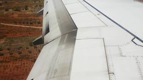 Vingsikt av flygplanklaffar som flyttar sig under blåsig landning arkivfilmer