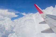 vingsikt för molnig himmel och flygplanfrån fönster Arkivfoto