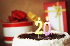 Vingt ans d'anniversaire Gâteau avec les bougies et les cadeaux brûlants Photos libres de droits
