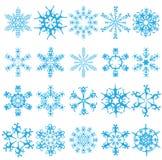 Vingt flocons de neige bleus sur un fond blanc. Photographie stock libre de droits