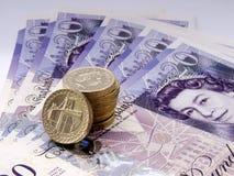 Vingt notes de livre sterling ont éventé avec la pile des pièces de monnaie Images libres de droits