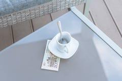 Vingt yuans chinois et tasse de café vide sur une table en verre de café extérieur Paiement, astuce photo stock