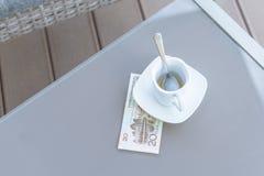 Vingt yuans chinois et tasse de café vide sur une table en verre de café extérieur Paiement, astuce image libre de droits