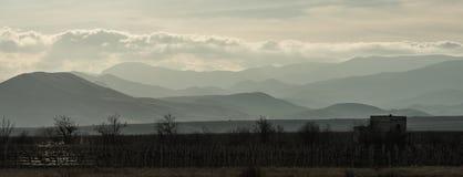 Vinhedo na máscara contra as montanhas e as nuvens nos raios do sol de ajuste foto de stock