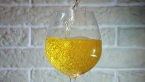 Vinho amarelo que derrama no vidro no movimento lento perto da dist?ncia filme