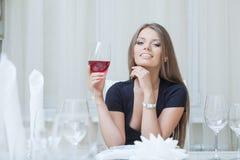Vinho bebendo de sorriso de encantamento da menina no restaurante fotografia de stock royalty free