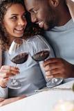 Vinho bebendo dos pares afro-americanos apaixonado no restaurante Fotografia de Stock