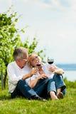 Vinho bebendo dos pares felizes no lago no verão Foto de Stock Royalty Free