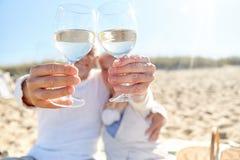 Vinho bebendo dos pares superiores felizes na praia do verão Imagens de Stock