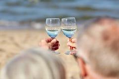 Vinho bebendo dos pares superiores felizes na praia do verão Foto de Stock Royalty Free
