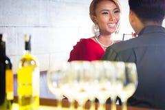 Vinho branco bebendo dos pares asiáticos na barra Foto de Stock