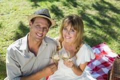 Vinho branco bebendo dos pares bonitos em um piquenique que sorri na câmera Imagem de Stock Royalty Free