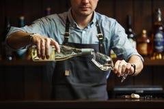 Vinho branco de derramamento do sommelier masculino em copos de vinho longo-provindos Foto de Stock Royalty Free
