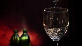 Vinho branco de derramamento no tiro de vidro, nas duas garrafas e no fundo vermelho, cálice de enchimento da bebida do álcool filme
