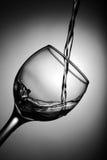 Vinho branco que derrama no vidro Fotografia de Stock Royalty Free