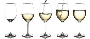 Vinho branco que está sendo derramado em um vidro de vinho vazio Fotografia de Stock Royalty Free