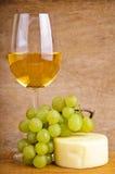 Vinho branco, uvas e queijo Fotografia de Stock